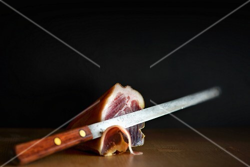 The end of a whole Prosciutto with a ham knife