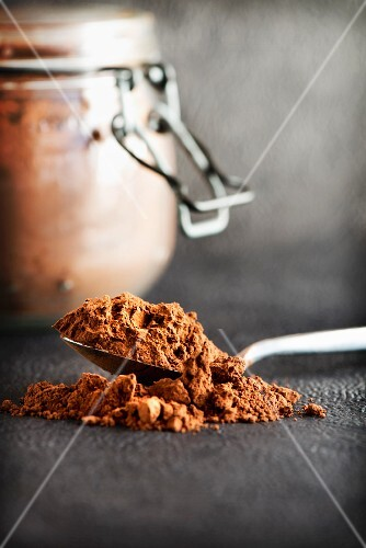 A teaspoon of cocoa powder with a preserving jar in the background