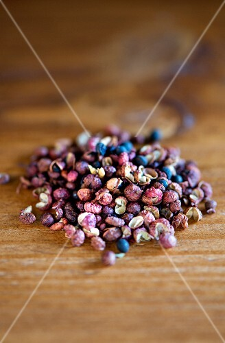 A pile of Szechuan peppercorns on a wooden table