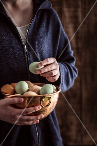 A woman holding a copper bowl of free range eggs