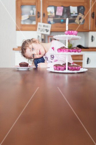 A blonde girl with blue eyes sitting in front of a stand of cupcakes
