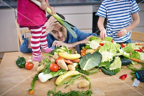 A desperate father with children in a kitchen surrounded by a chaotic pile of vegetables