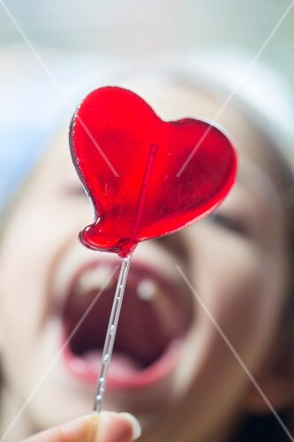 A heart-shaped lolly with a woman in the background with her mouth wide open