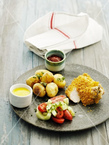 A chicken leg with a cornflakes crust and oven-roasted potatoes