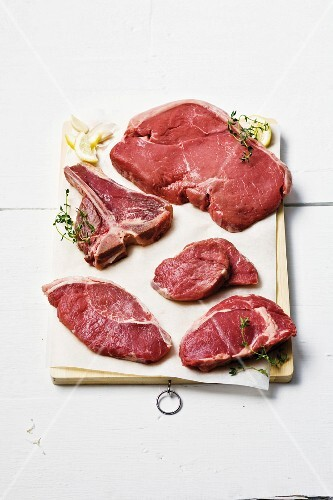 Five different beef steaks on a wooden board