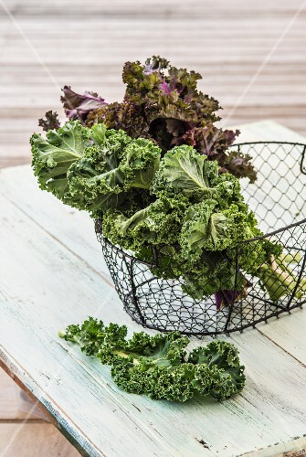 Green and purple kale leaves in a wire basket