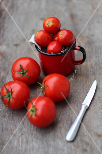 Tomatoes with a knife on a wooden surface