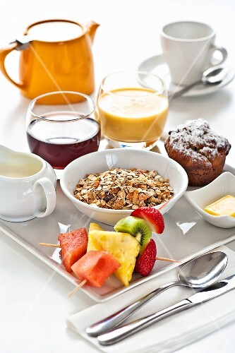 A breakfast tray with muesli, fruit, a muffin, juice and tea
