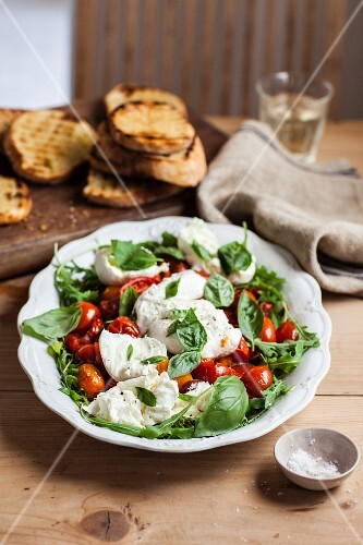 Braised tomatoes with mozzarella, rocket and basil