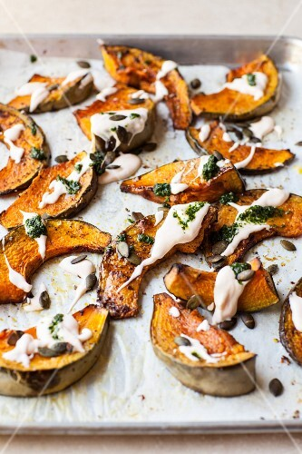 Roasted pumpkin wedges with mayonnaise, pesto and pumpkin seeds on a baking tray