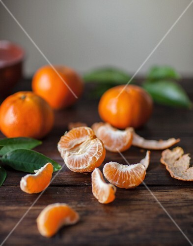Clementines on a wooden surface, one peeled and split into segments