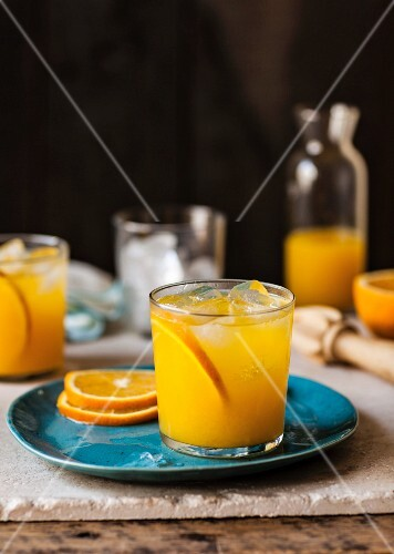 A glass of orange juice with fruit slices of ice cubes