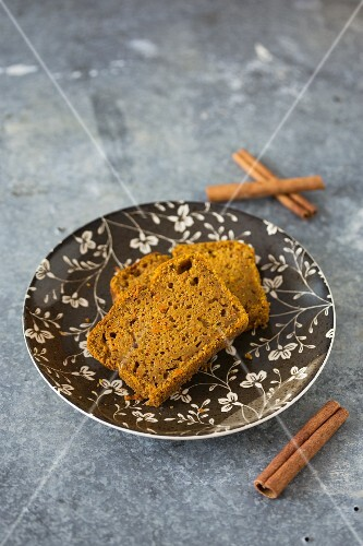 Two slices of carrot cake with cinnamon on a plate