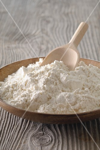 Flour in a wooden bowl with a wooden scoop