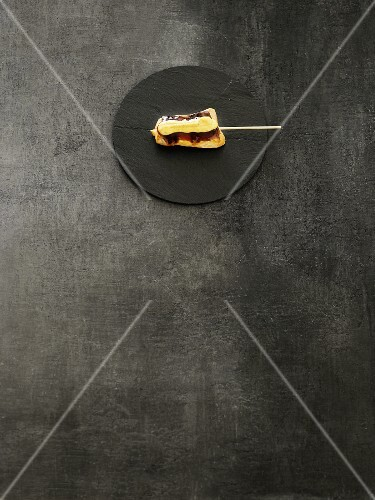 A kushi skewer on a black stone platter