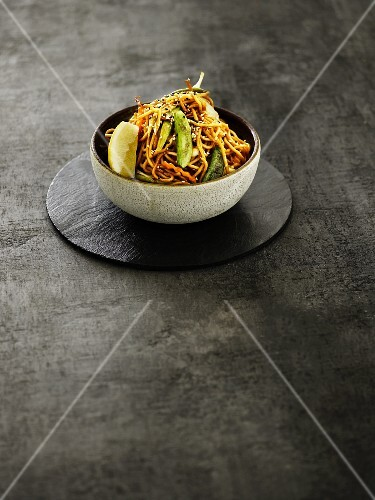 An Oriental vegetable dish with fried noodles and lemon