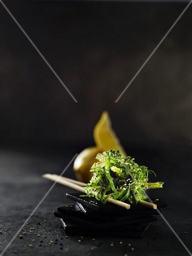 Sesame seed seaweed and chopsticks on a black slate dish