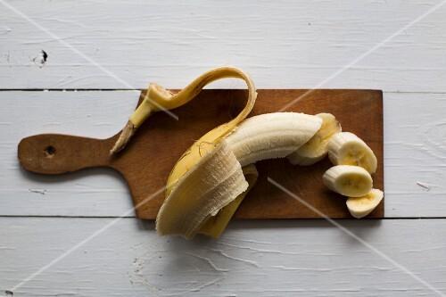 A banana on a wooden chopping board