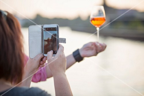 A woman photographing a drink with her smart phone