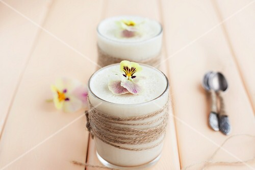 Light lemon cream with pansies on a light wooden surface