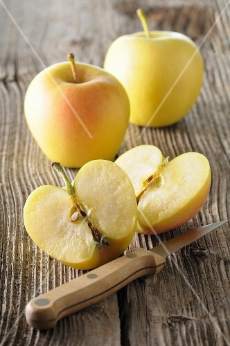 Golden Delicious apples, whole and halved, on a wooden surface