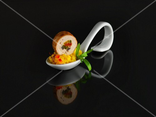 Saffron risotto and pork roulade on a serving spoon