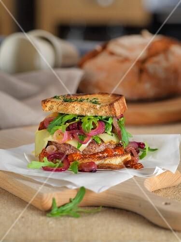 A rye bread burger on a wooden board