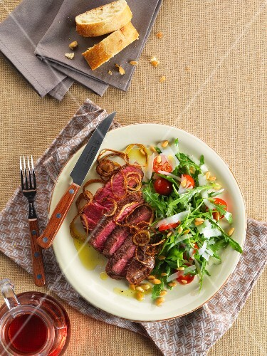 Beef steak with roasted onions and a rocket salad