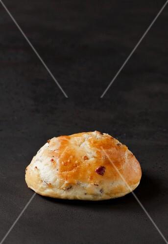 A burger bun with onions on a dark surface