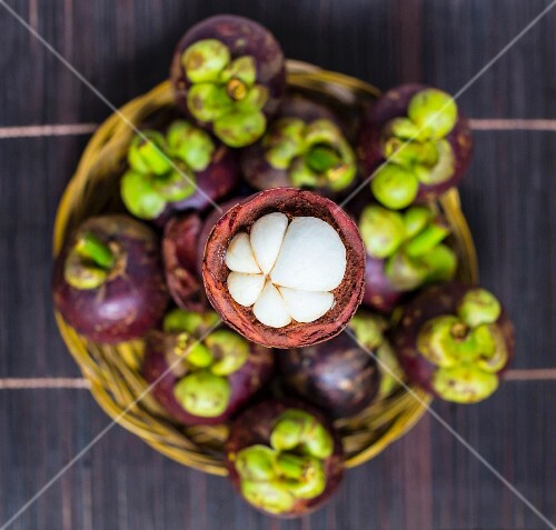 Fresh mangosteens in a basket (seen from above)