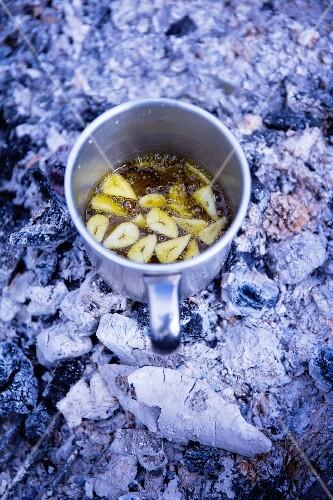 Garlic flavoured olive oil in a tin mug