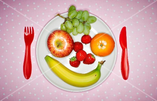 A face made from fresh fruit on a plate with plastic cutlery (seen from above)