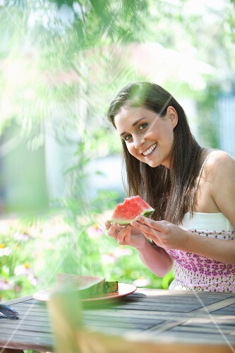 A young woman sitting at a summer garden table eating a watermelon