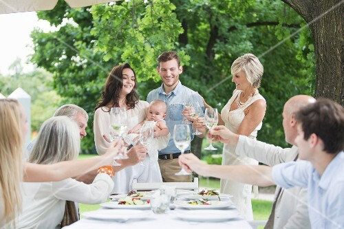 Family garden party: a family raising a toast to a young couple with a baby