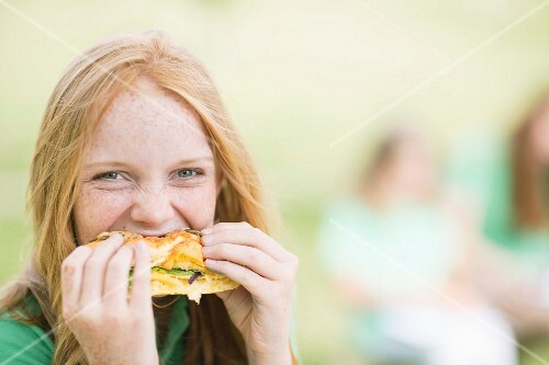 A red haired teenager biting into a sandwich