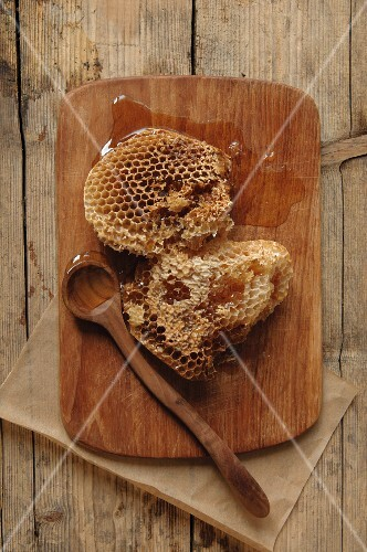 Honeycomb from wild bees on a wooden board with a wooden spoon
