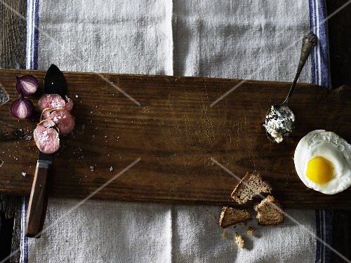 An arrangement featuring a fried egg, cheese and roast meat on a wooden board