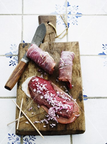 Raw beef roulade with ham and chopped onions