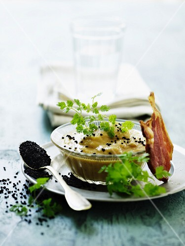 Cream of cauliflower soup with smoked fish and black sesame seeds