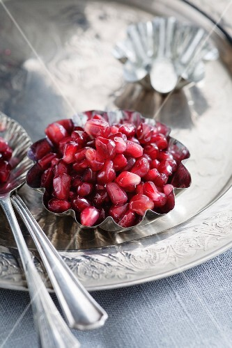 Pomegranate seeds in a metal bowl