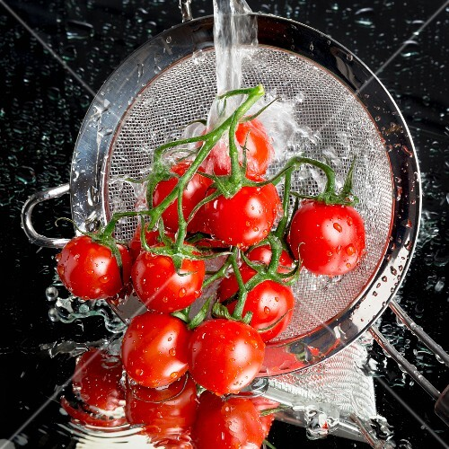 Tomatoes being washed in a sieve