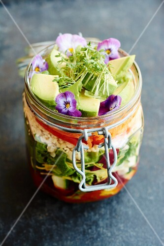 A mixed leaf salad with avocado and edible flowers in a flip-top jar to takeaway