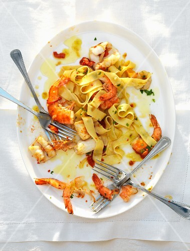 A half eaten plate of pappardelle with seafood and four forks