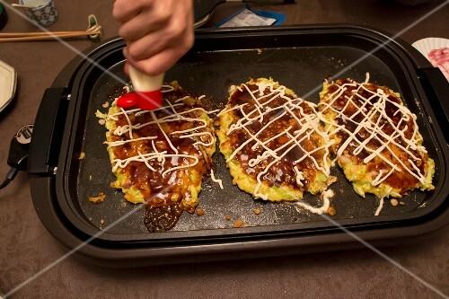 Okonomiyaki (Japanese pancakes) on a hot tray being decorated with mayonnaise