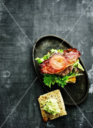 A burger on a roll with crispy bacon and lettuce