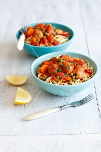 Spaghetti with tuna dumplings in tomato sauce with peas