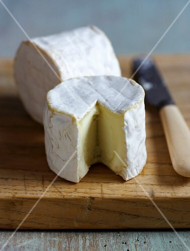 Sliced soft cheese on a chopping board