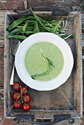 Wild garlic soup on a wooden tray with wild garlic leaves and tomatoes