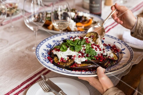 A woman serving oven roasted aubergines with Greek yoghurt and pomegranate seeds