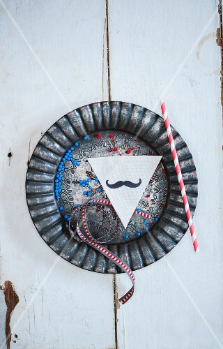 A ribbon, a straw, a paper moustache and sugar pearls on a metal plate